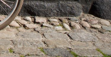 Wheel and bumpy cobblestones.
